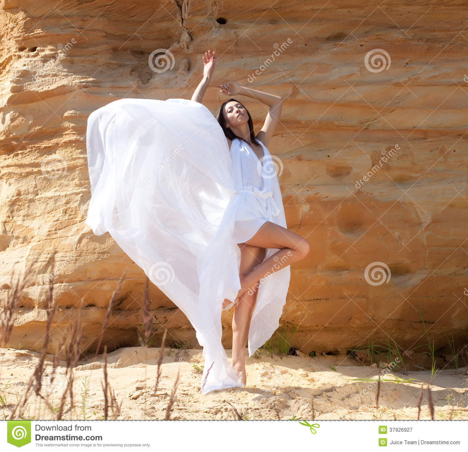 Женщина в белых танцах платья на пустыне