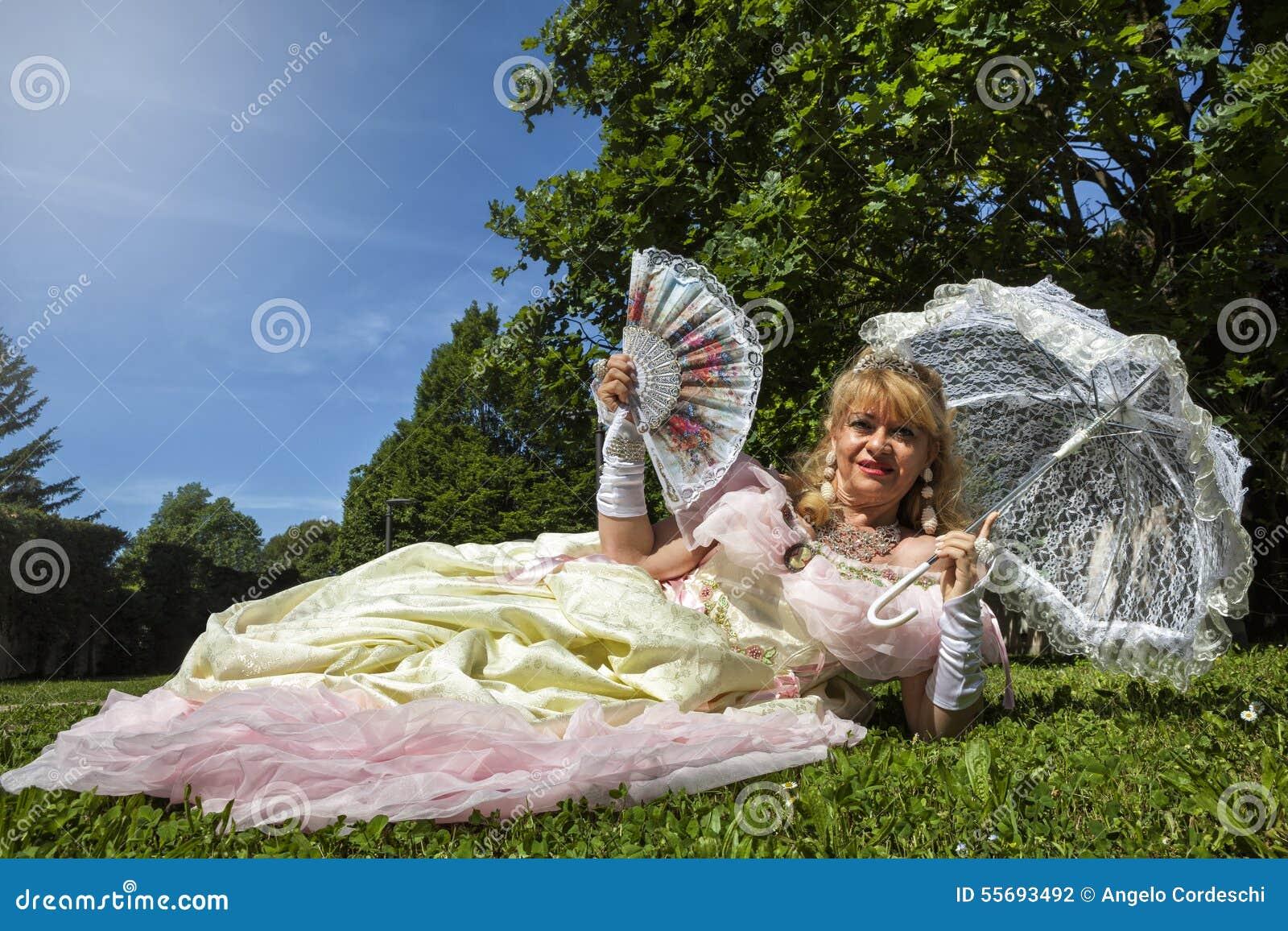 Женщина в венецианском костюме лежа на зеленом парке с белым зонтиком
