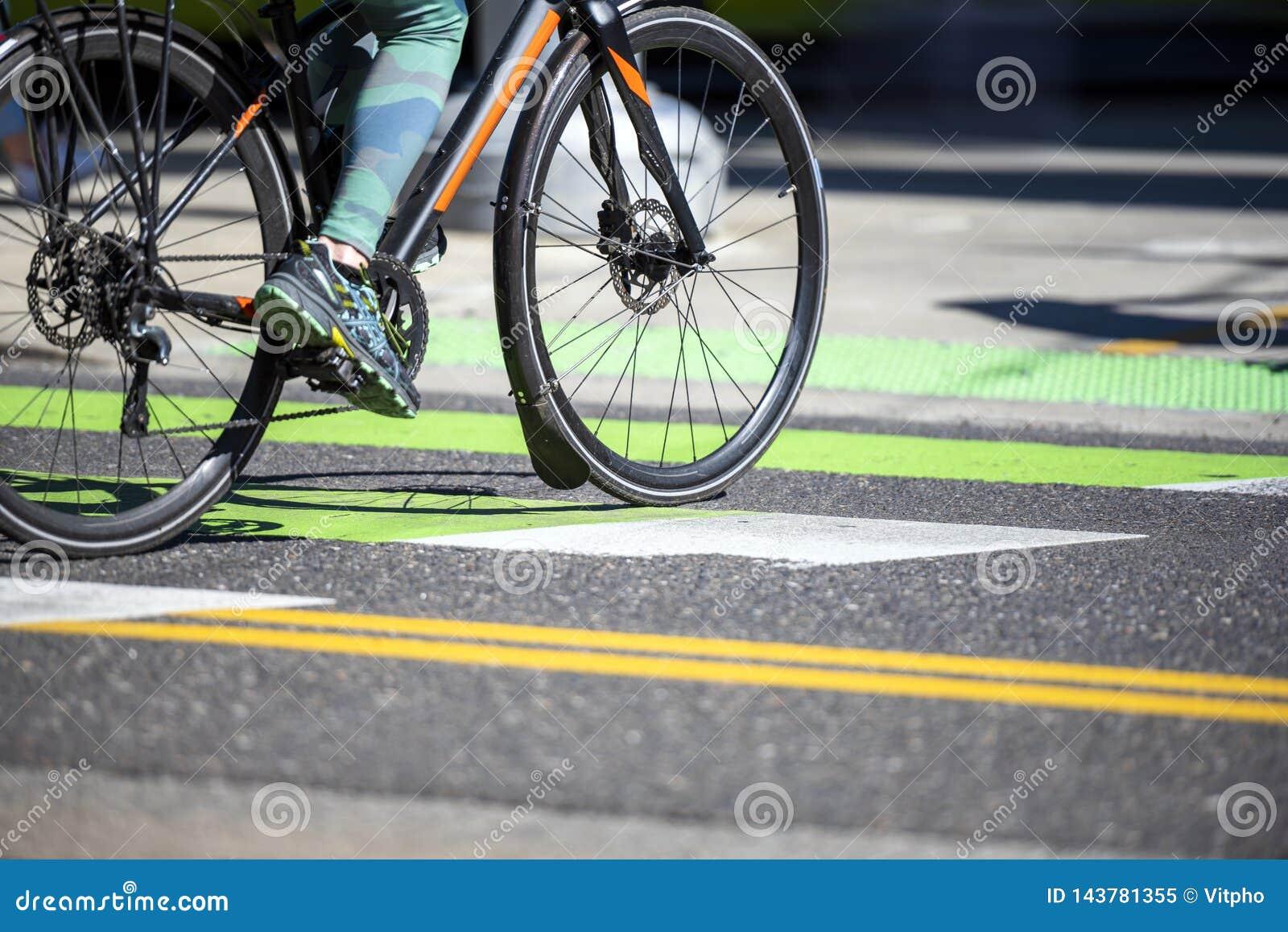 Женщина в гетры путешествуя через город на велосипеде пересекает дорогу на пешеходный переход