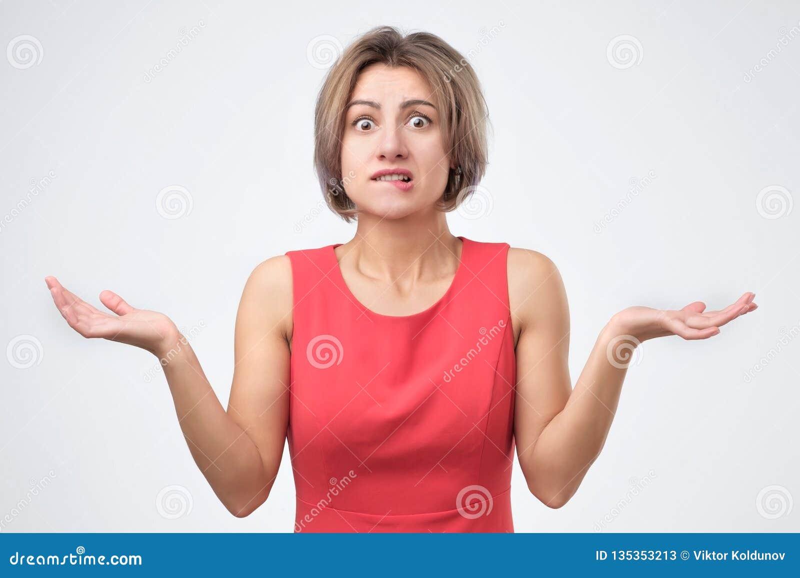 Женщина в голубых одеждах shrugging ее плечи, выражая сомнение, неопределенность или равнодушие