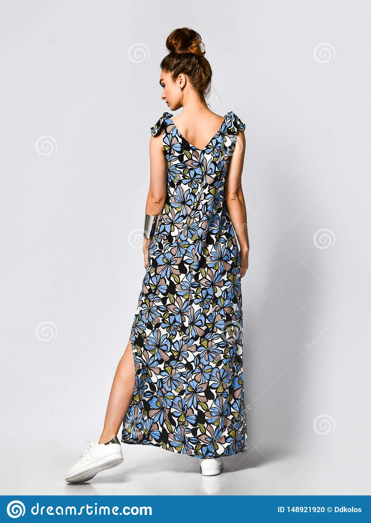 Женщина в длинном флористическом платье в магазине моды - портрете девушки в магазине одежды в макси платье лета