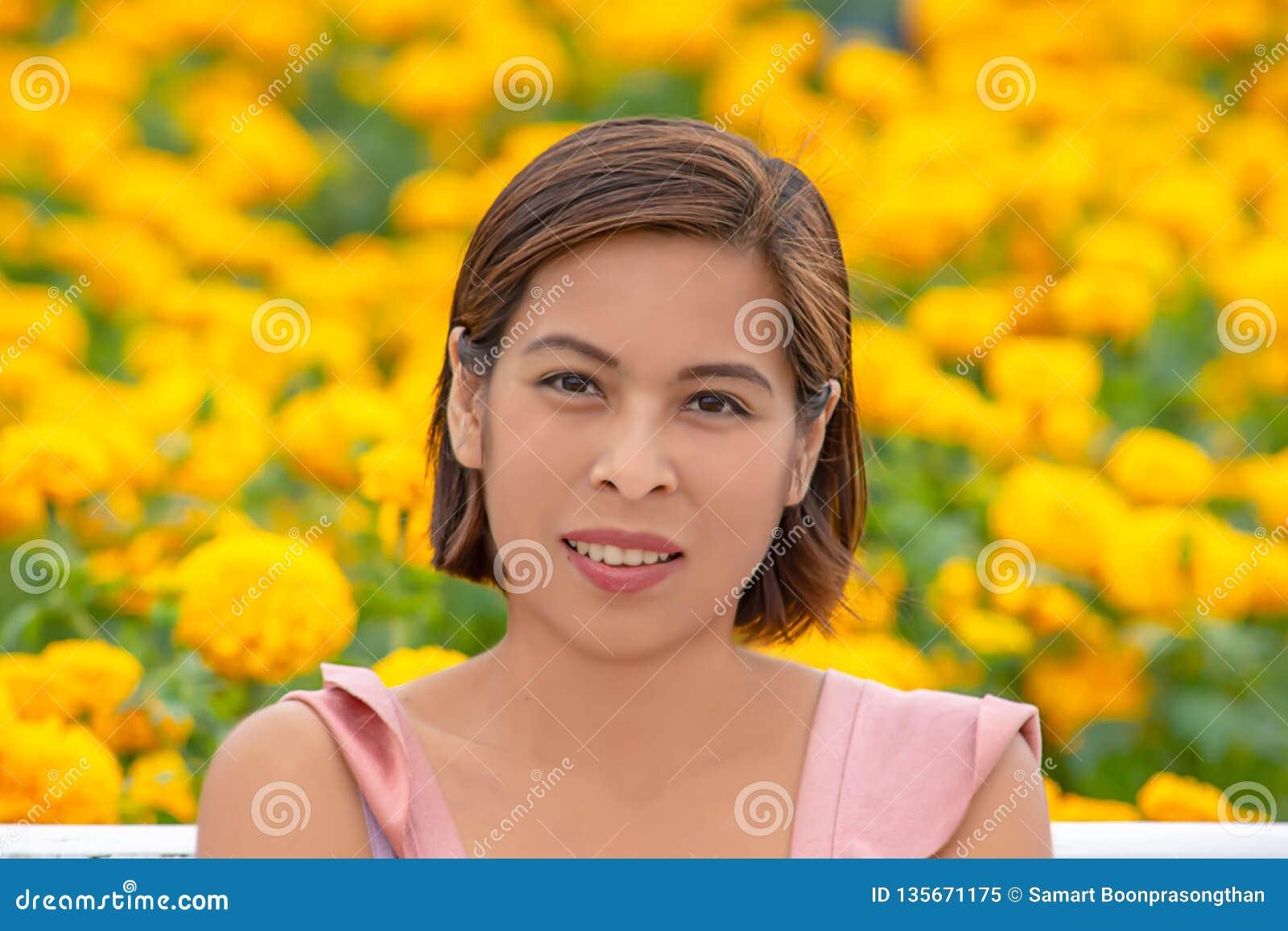 Женщина в желтом саде цветков ноготк или erecta Tagetes на Phu Rua, Loei в Таиланде