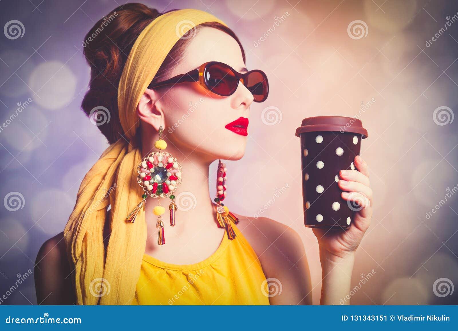 Женщина в желтых одеждах с кофе