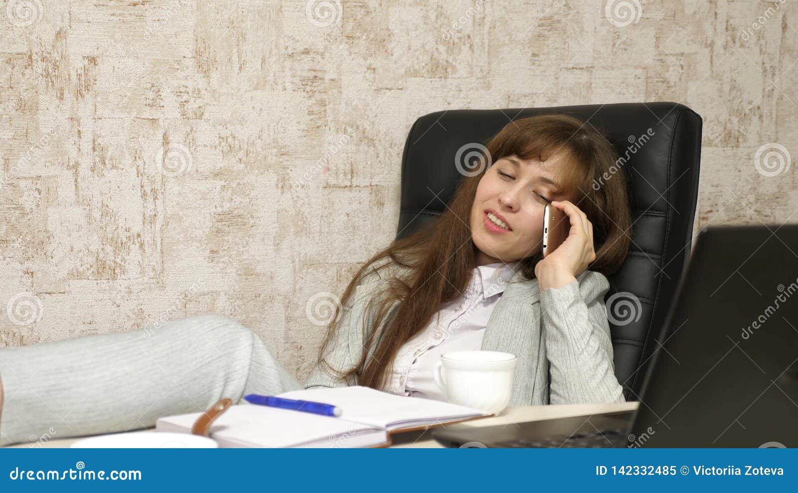 Женщина в кофе офиса выпивая отдыхая в рабочем месте красивая коммерсантка с телефоном сидит в стуле с босыми ногами