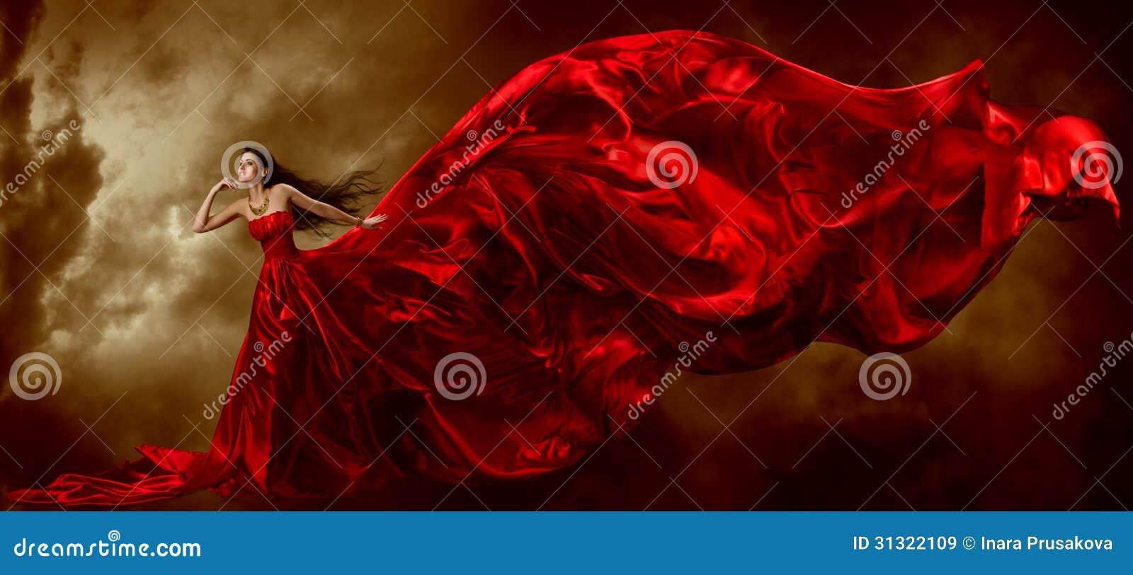 Женщина в красном платье с развевать красивая ткань