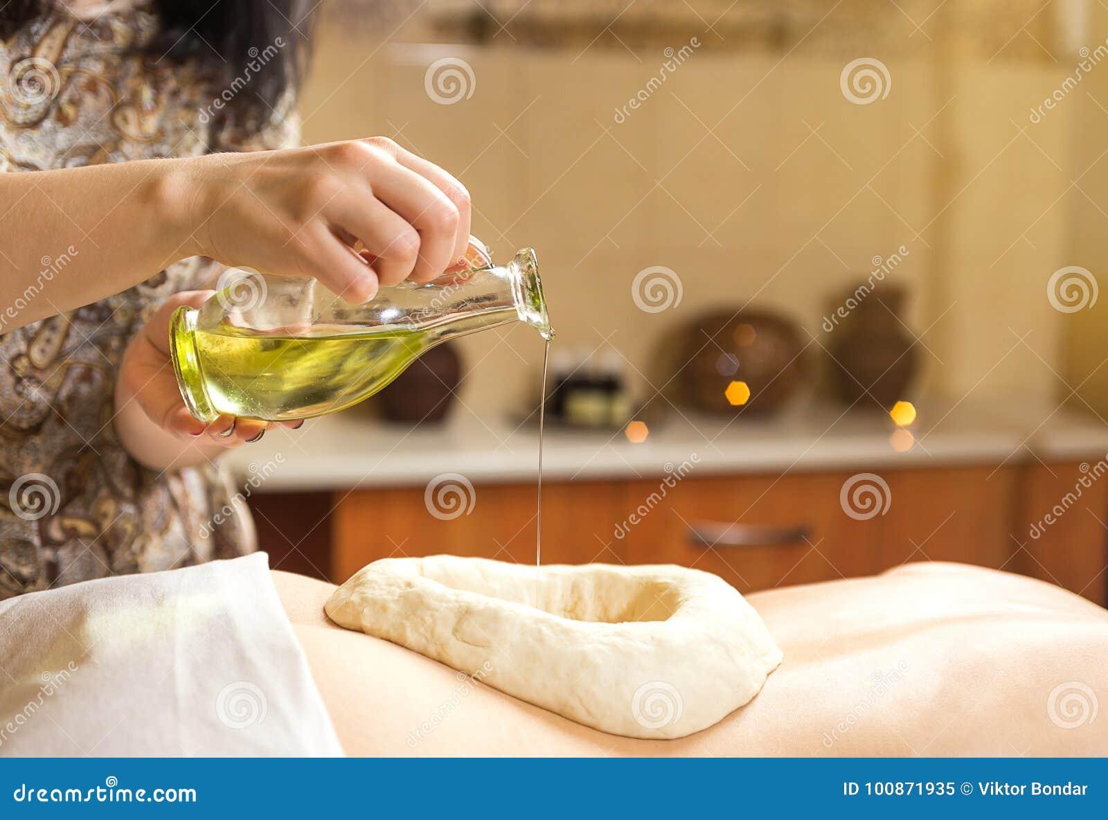 Женщина в курорте здоровья имея массаж терапией ароматности с essentia