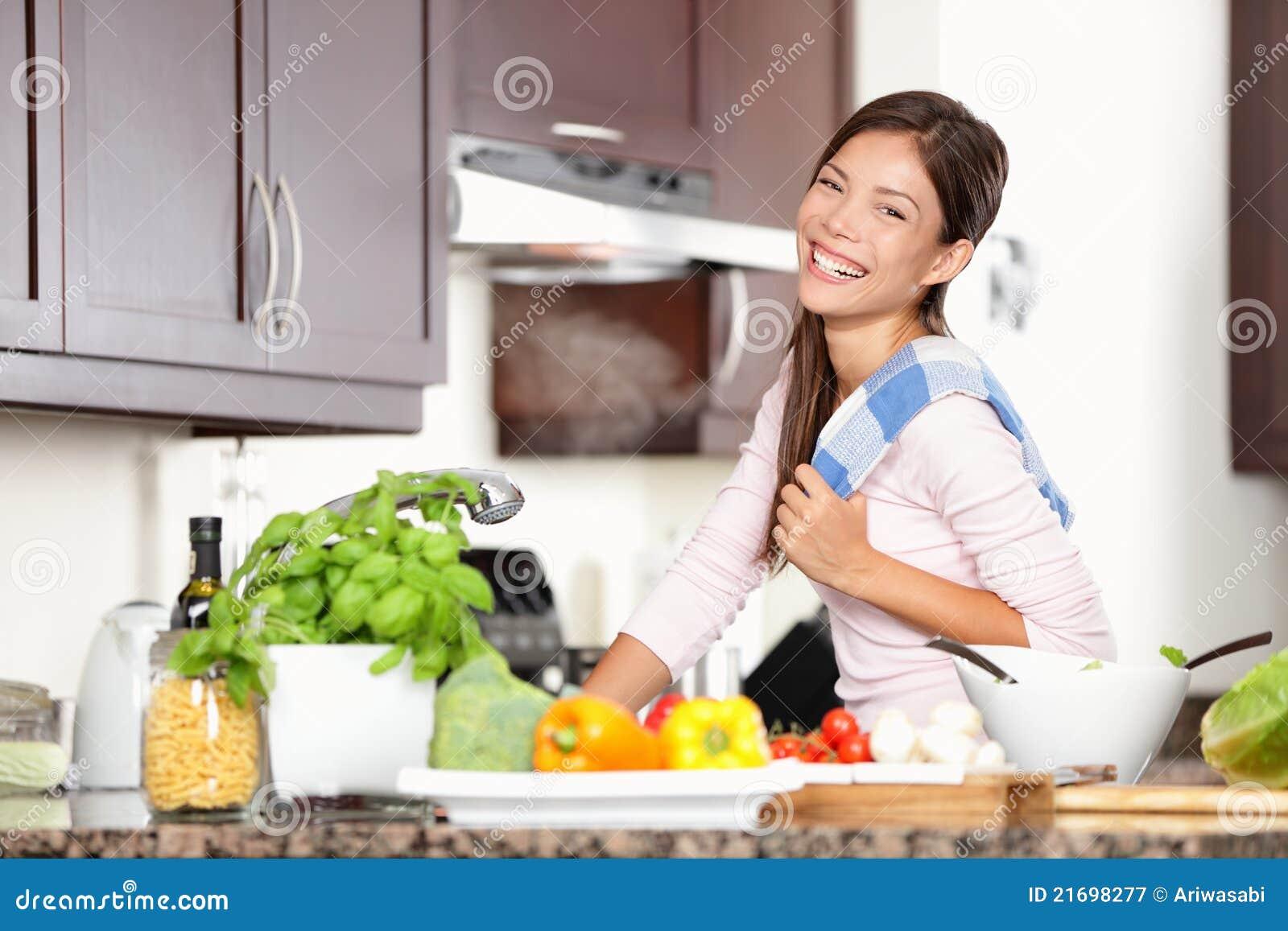 Женщина в кухне делая еду счастливым