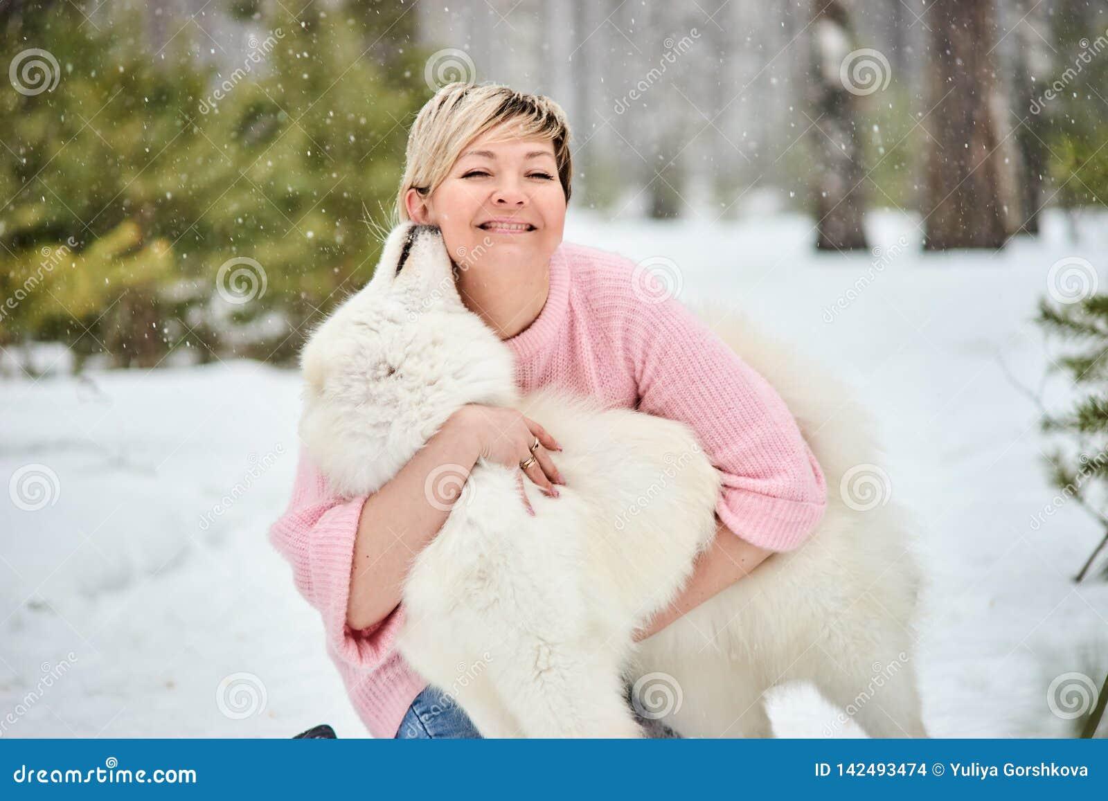 Женщина в лесе зимы идя с собакой Снежок падает