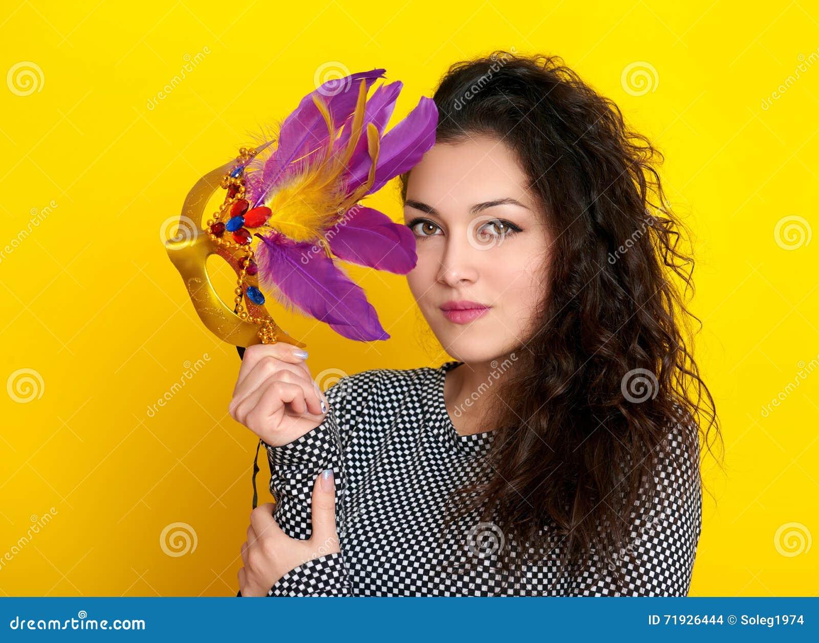 Женщина в маске масленицы с пером, красивым портретом девушки на желтой предпосылке цвета, длинном вьющиеся волосы