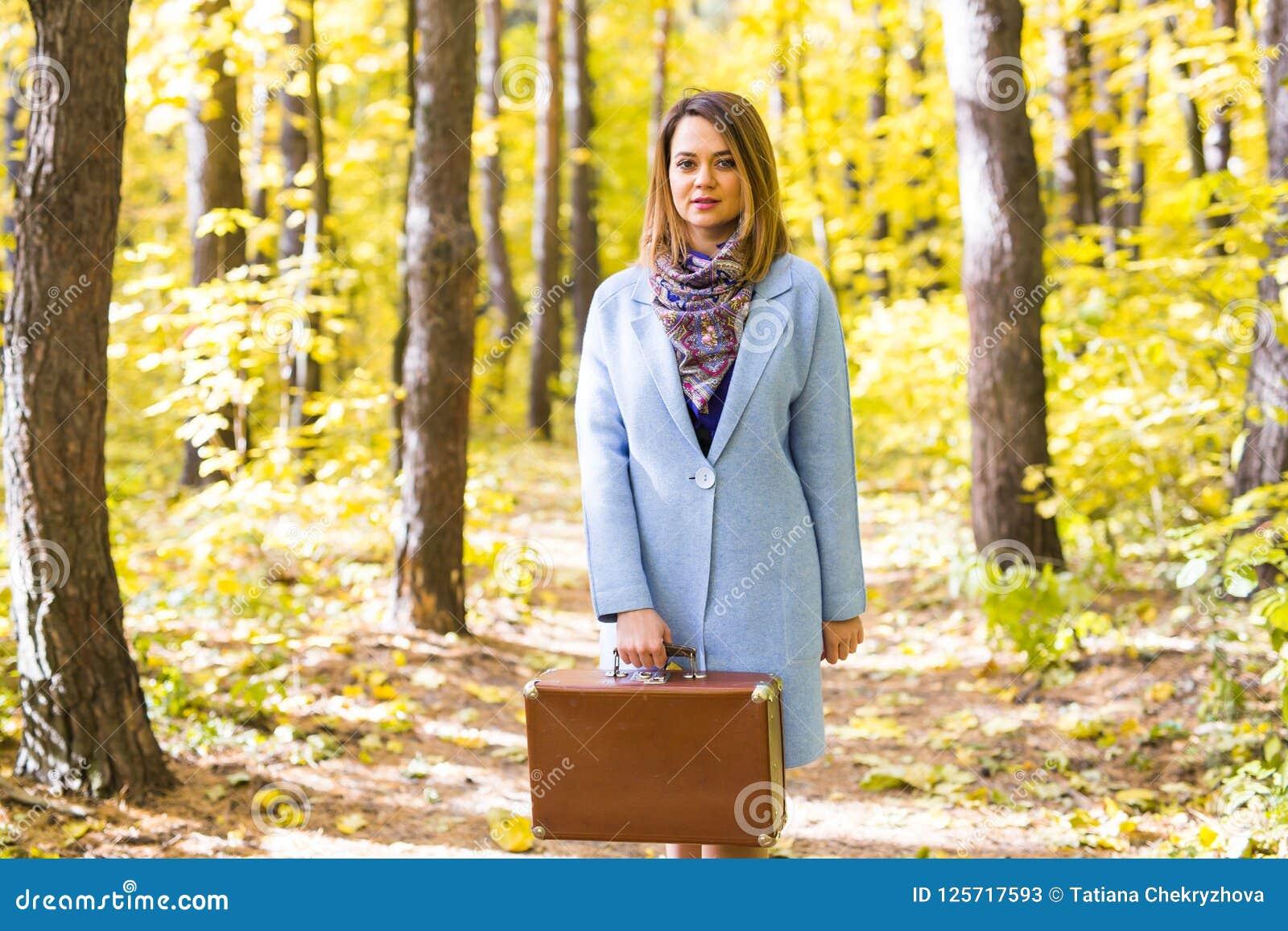 Женщина в парке осени идя с чемоданом