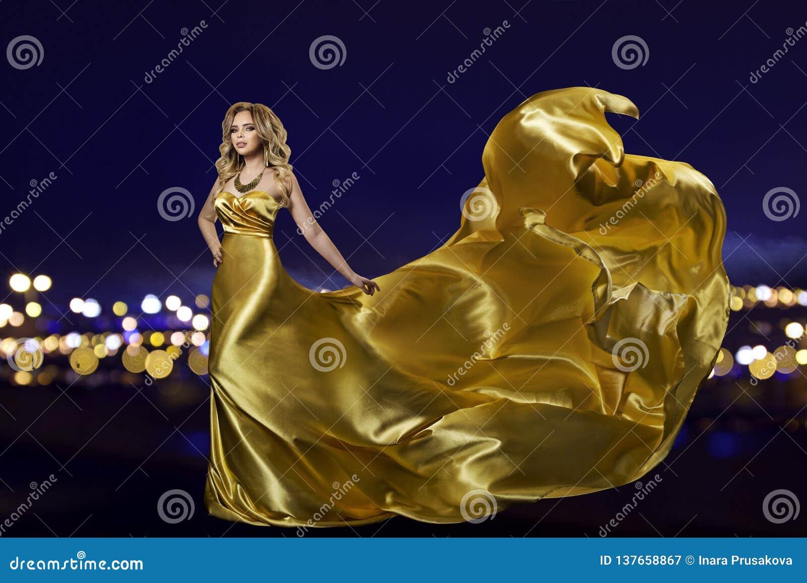 Женщина в платье золота над городом ночи, фотомоделью в длинной золотой мантии, развевая ткани