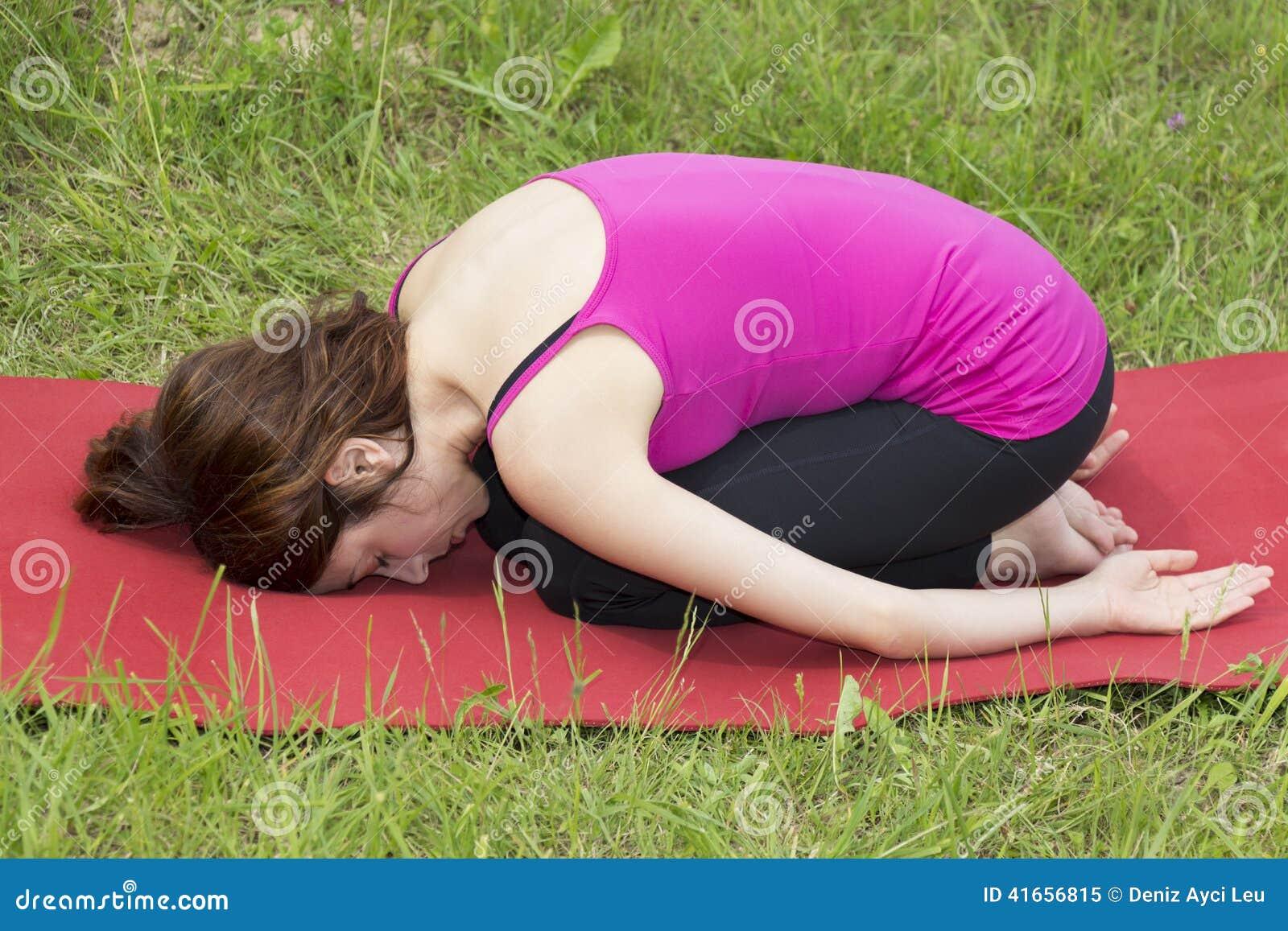 Женщина в представлении Childs во время йоги outdoors