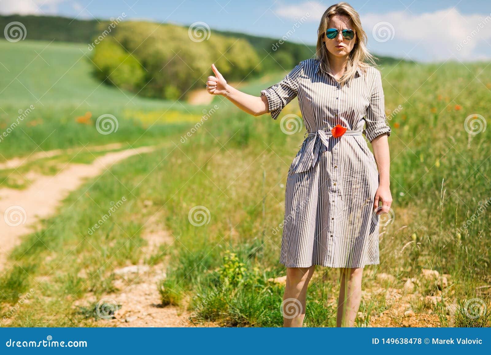 Женщина в путешествовать автостопом с дороги во время солнечного дня