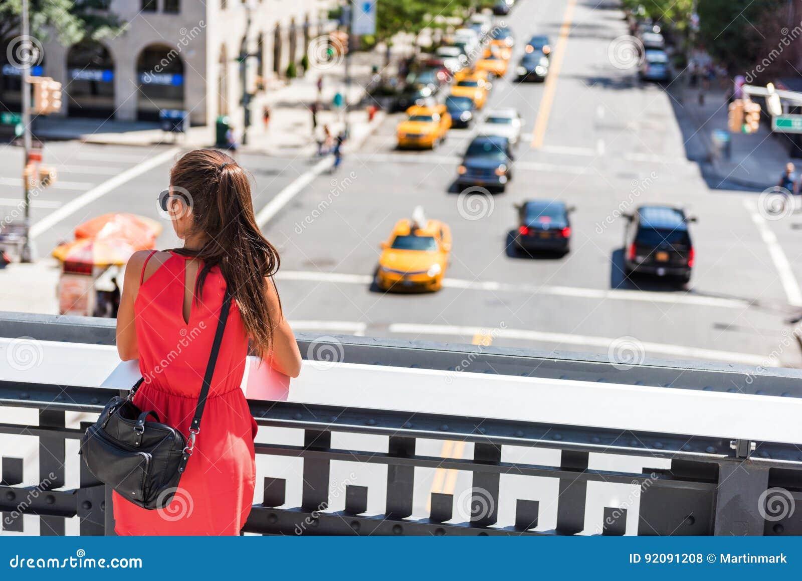 Женщина в улице Нью-Йорка наблюдая от высокой ветки