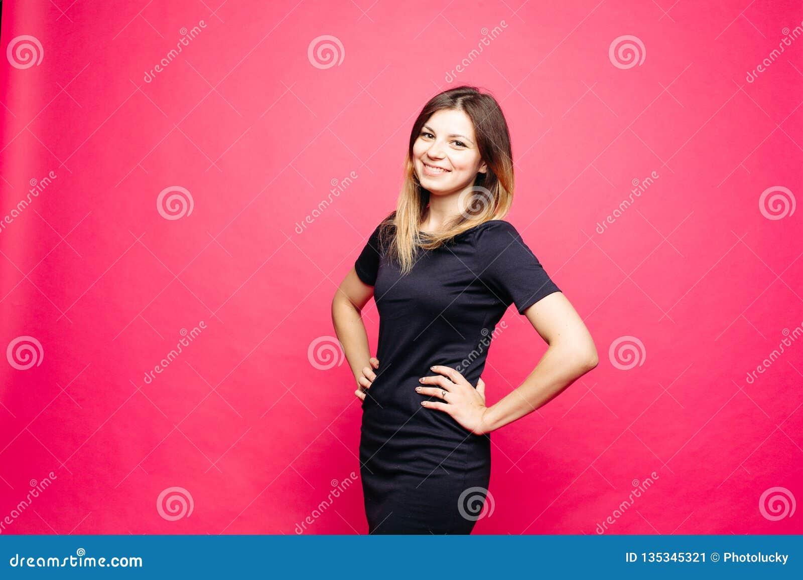 Женщина в черном платье lauthing emotionaly представлять с руками на талии