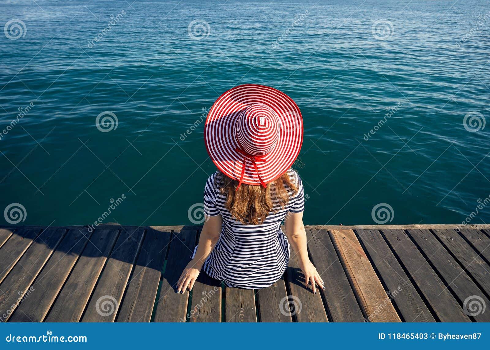 Женщина в шляпе на деревянной пристани
