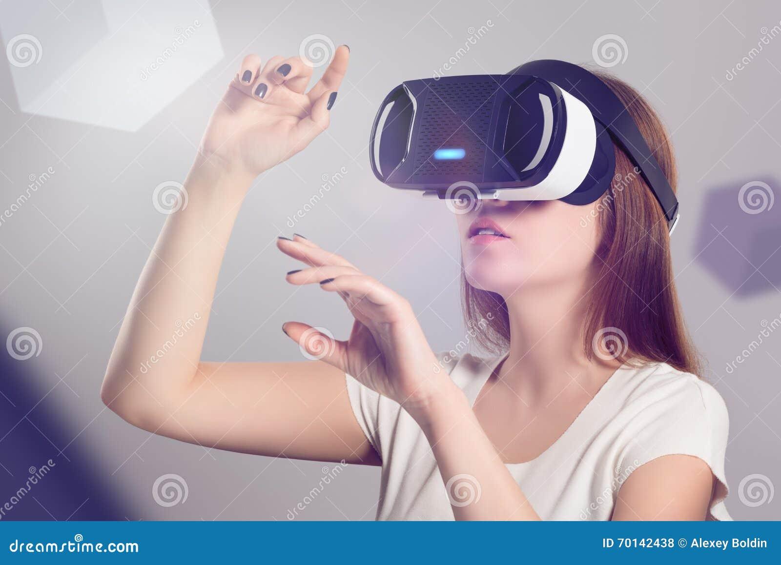 Женщина в шлемофоне VR смотря вверх и пробуя касаться объекты