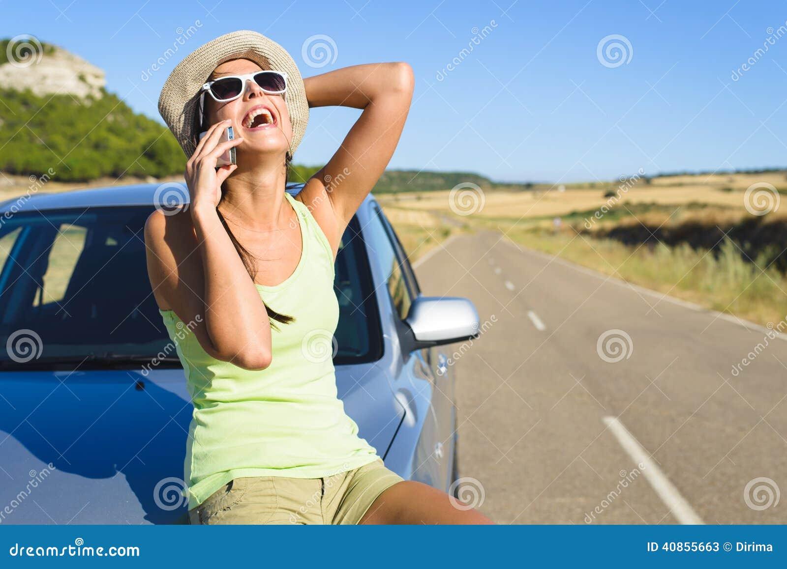 Женщина говоря на мобильном телефоне во время автомобильного путешествия лета