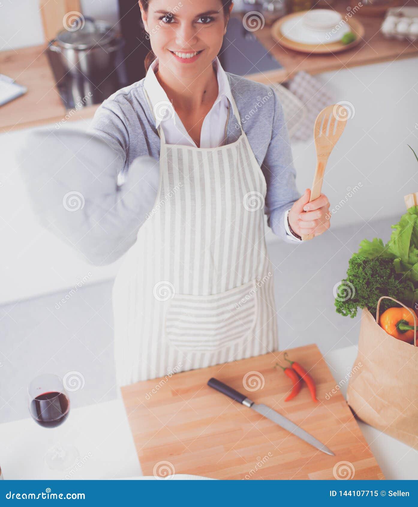Женщина делая здоровую еду стоя усмехающся в кухне