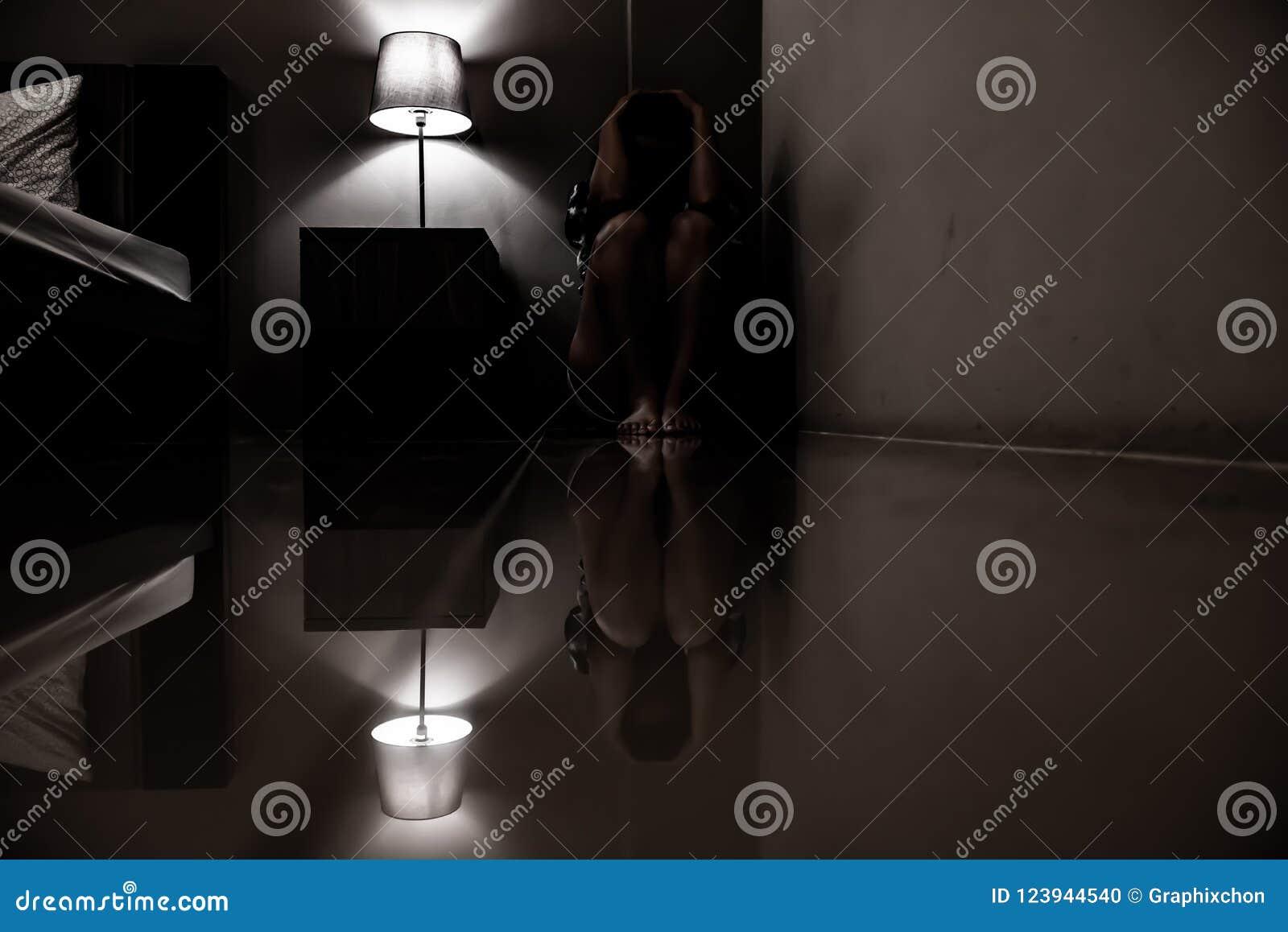 Женщина депрессии самостоятельно в темной комнате Проблема психических здоровий, PTSD