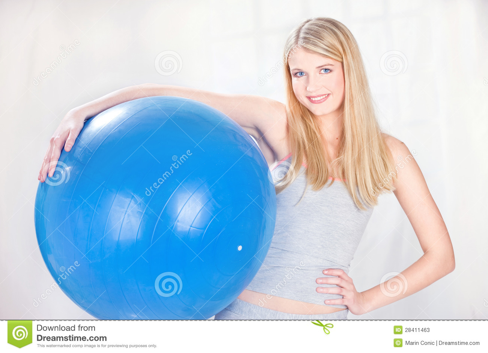 Женщина держа голубой шарик pilates