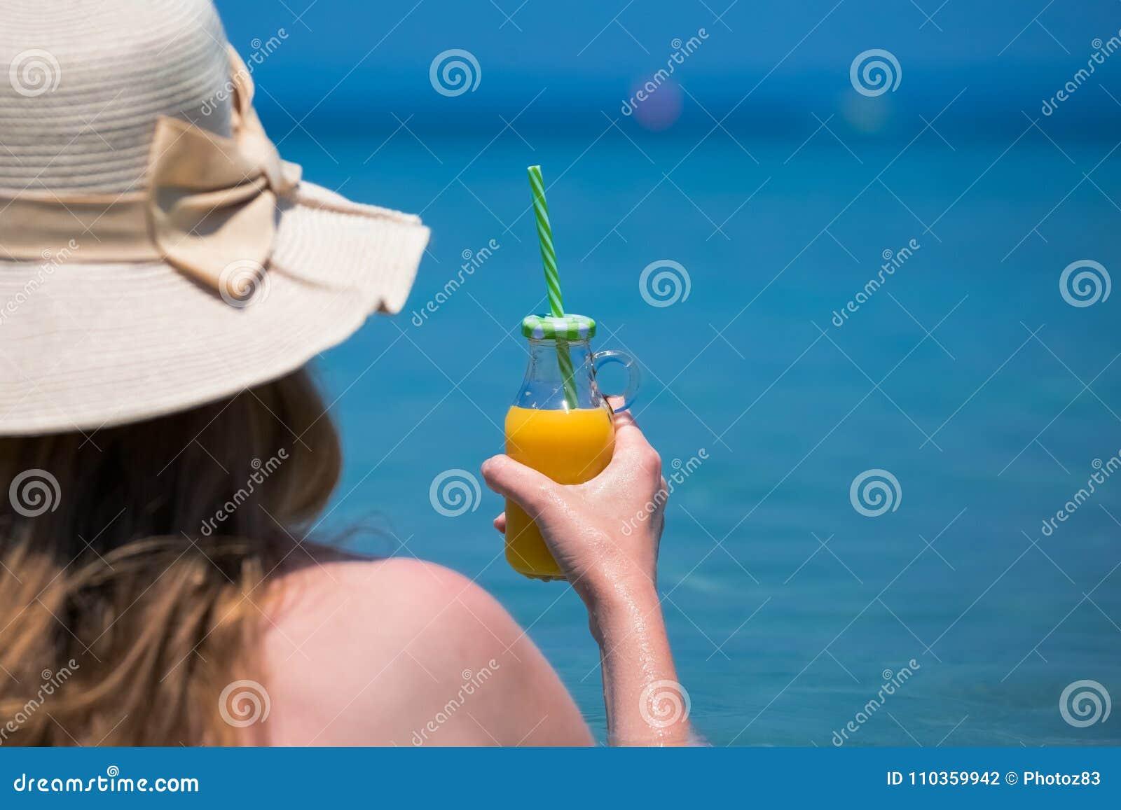 Женщина держа стеклянную бутылку свежего апельсинового сока и смотря