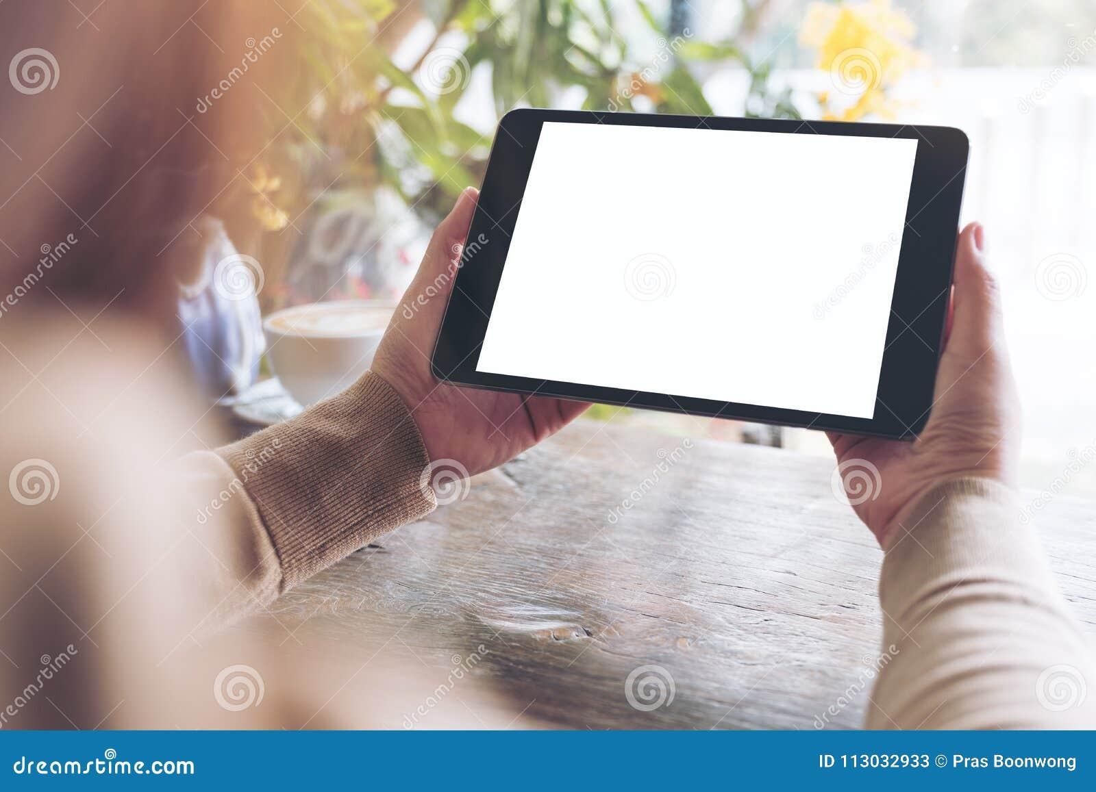 Женщина держа черный ПК таблетки с пустым белым экраном настольного компьютера в кафе