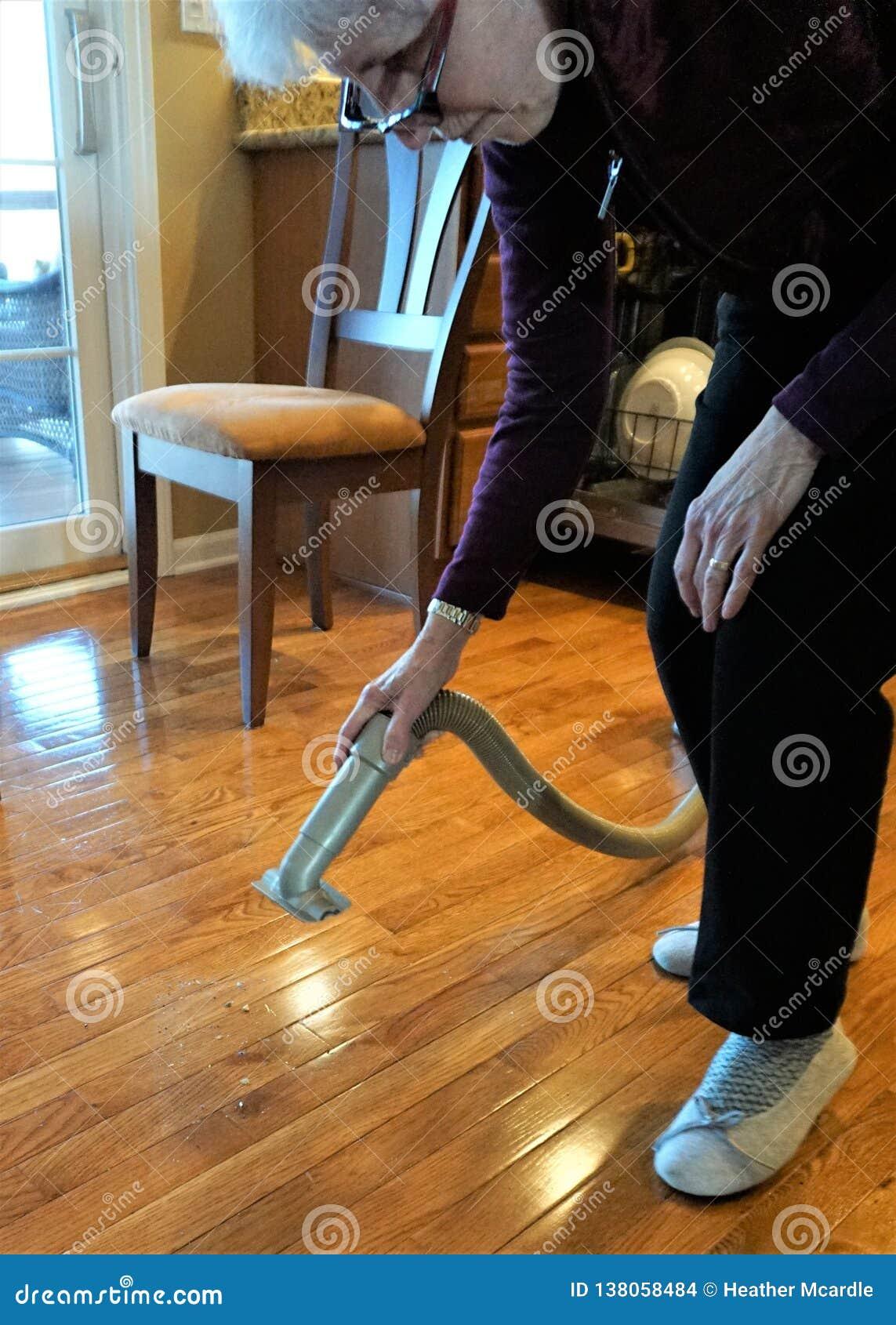 Женщина держит вакуум над грязным полом