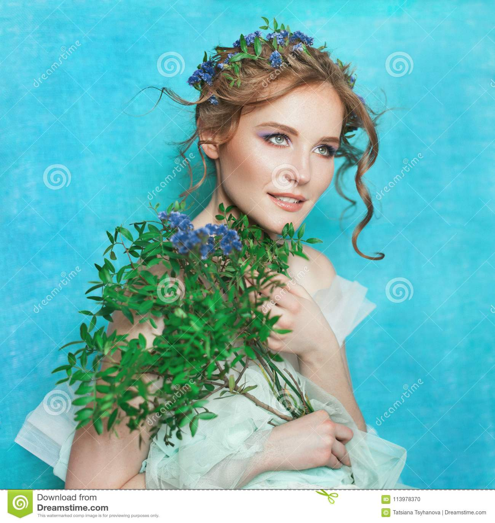 Женщина детенышей усмехаясь нежная с голубыми цветками на свете - голубой предпосылке Портрет красоты весны