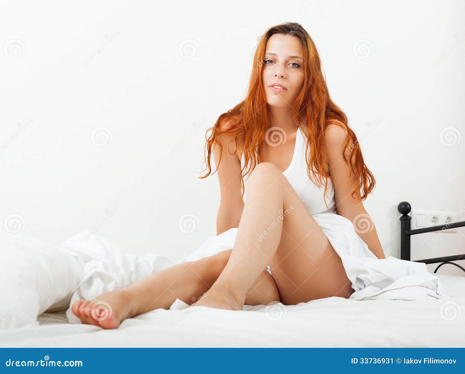 Женщина лежа на белых листах на кровати дома