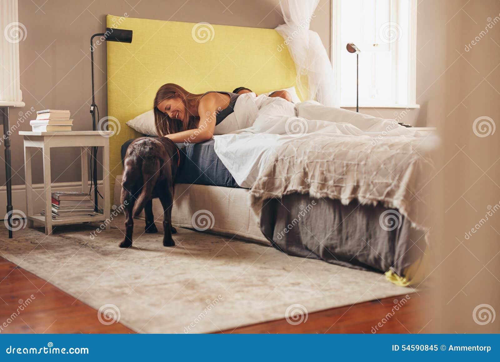 Женщина лежа на кровати играя с ее собакой в утре