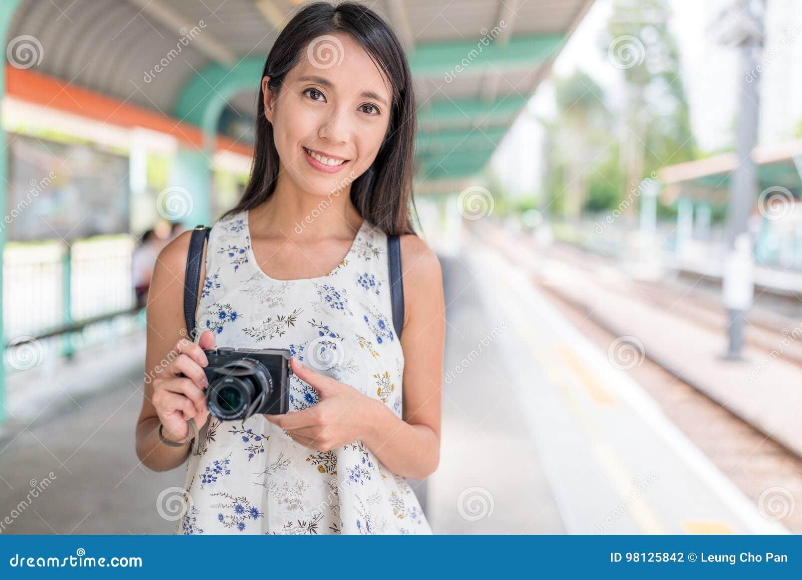 Женщина держа цифровой фотокамера в светлой железнодорожной станции