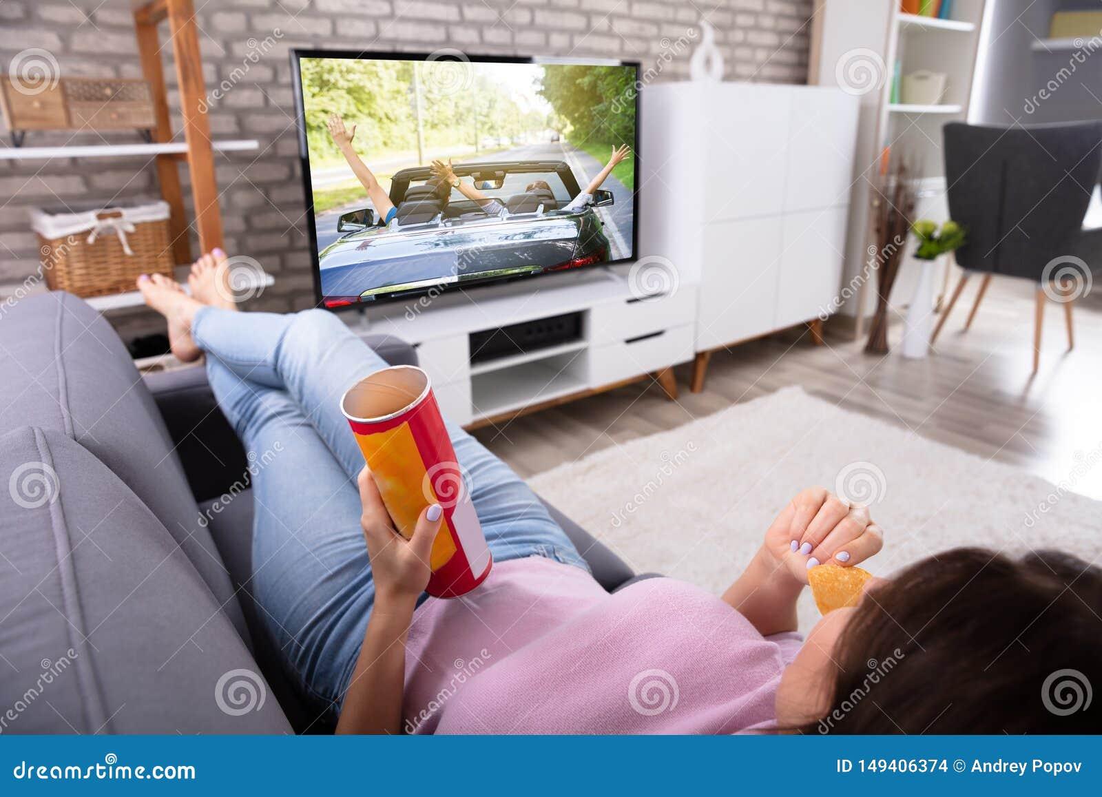 Женщина есть картофельные чипсы пока смотрящ телевидение