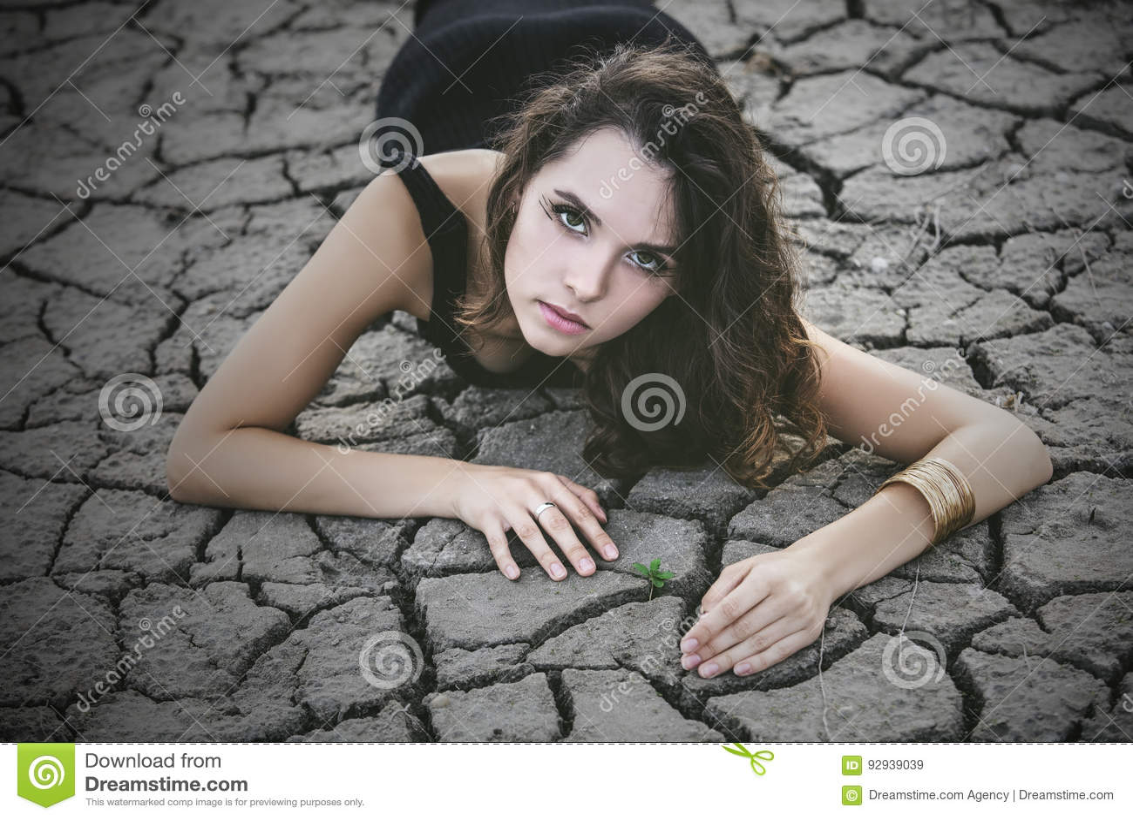 Женщина защищает малый росток на треснутой почве пустыни