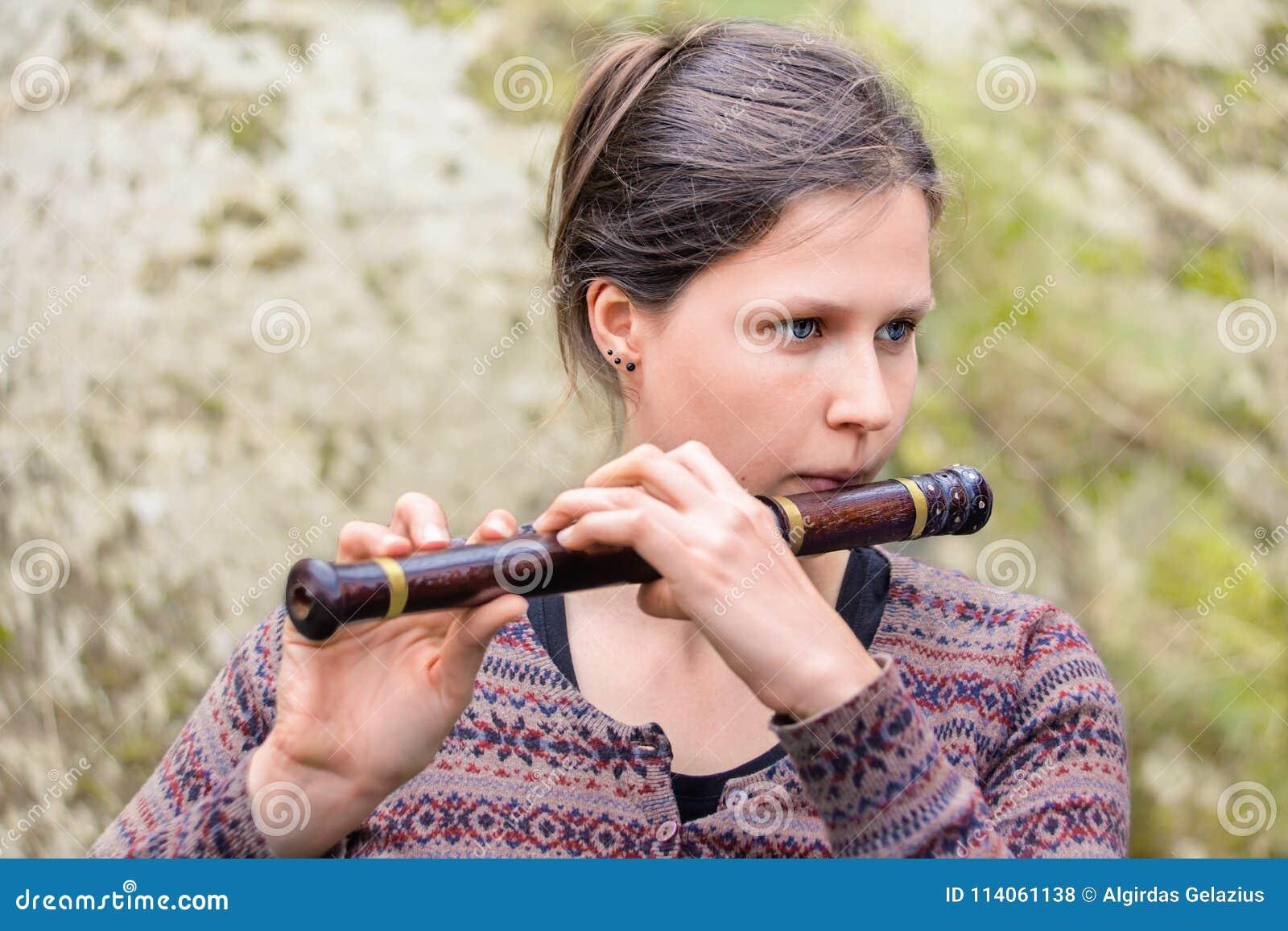 Женщина играя индийскую деревянную каннелюру