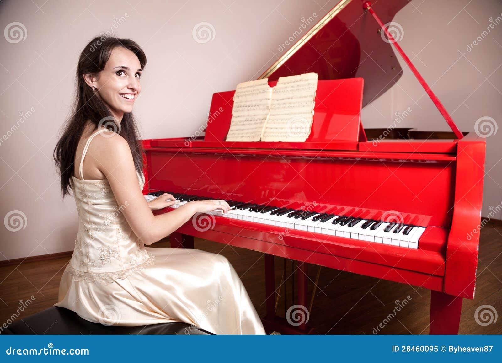 Женщина играя красный грандиозный рояль