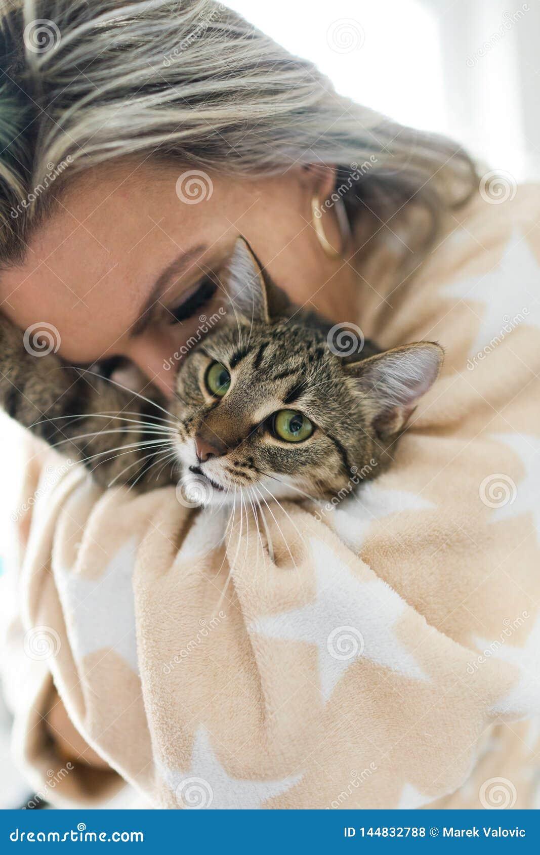 Женщина играя с котом - обнимающ и целующ