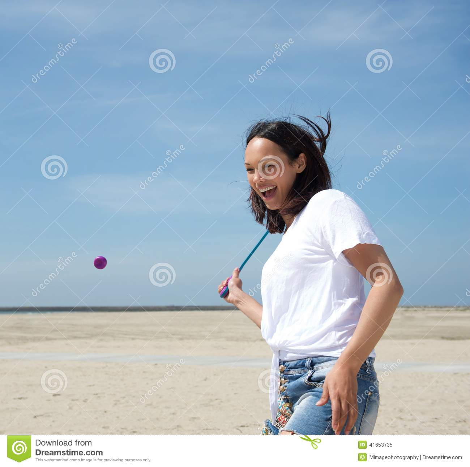 Женщина играя теннис на пляже