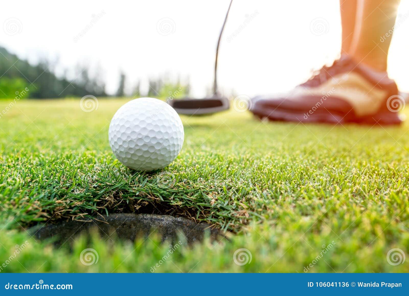 Женщина игрока в гольф азиатская кладя шар для игры в гольф на зеленый гольф на времени вечера солнца установленном
