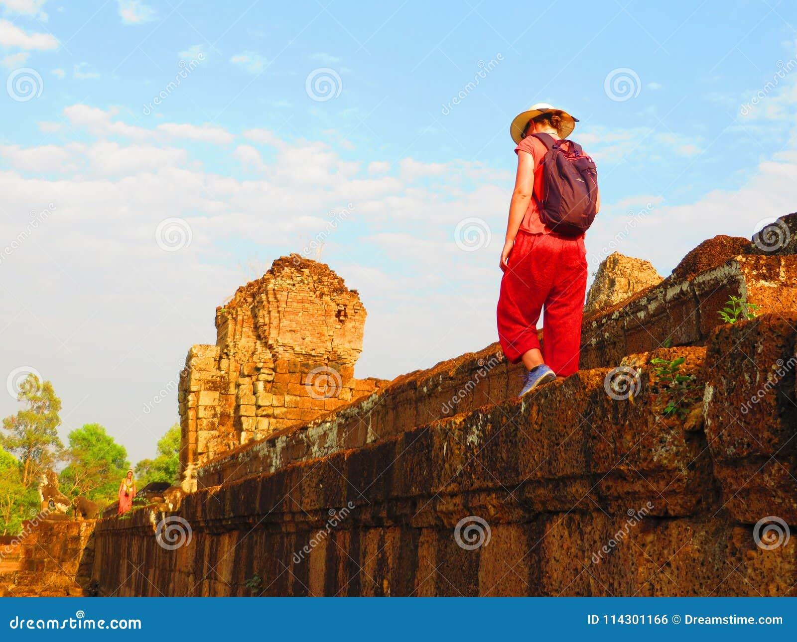 Женщина идя на краю стены в Angkor, Камбодже