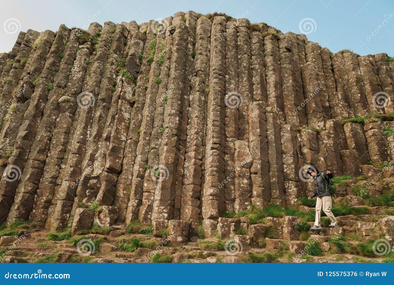 Женщина идя среди шестиугольных камней на гигантской мощёной дорожке ` s