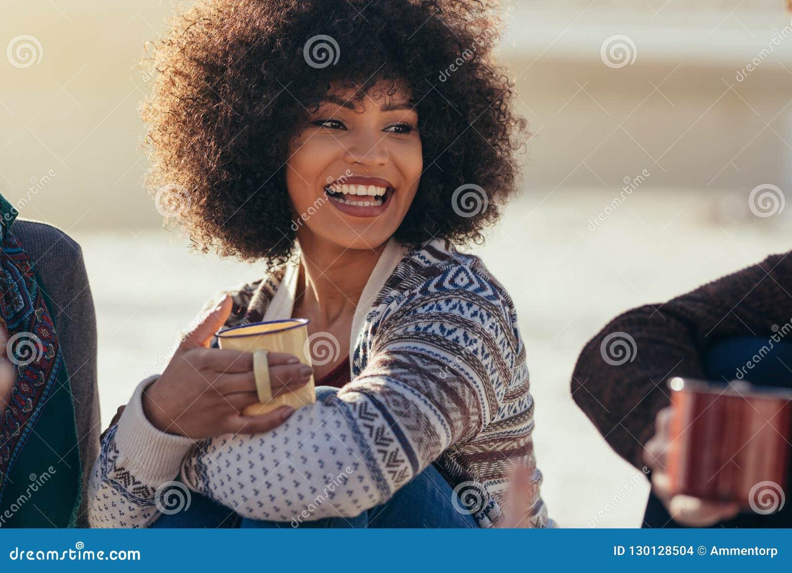 Женщина имея кофе с друзьями на пляже