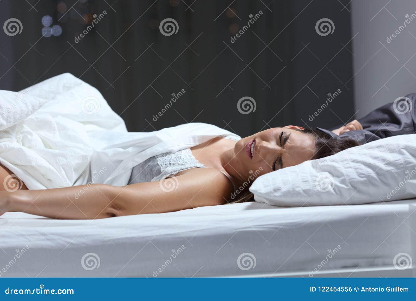 Женщина имея кошмар в кровати в ноче