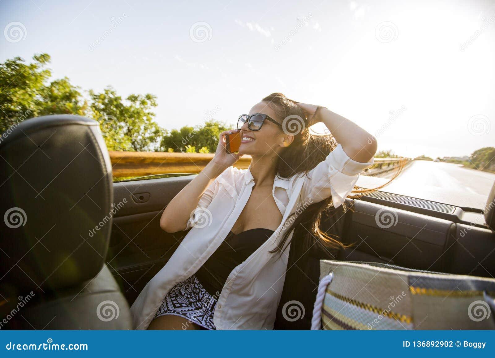 Женщина использует мобильный телефон и распологать в cabriolet на летнем дне