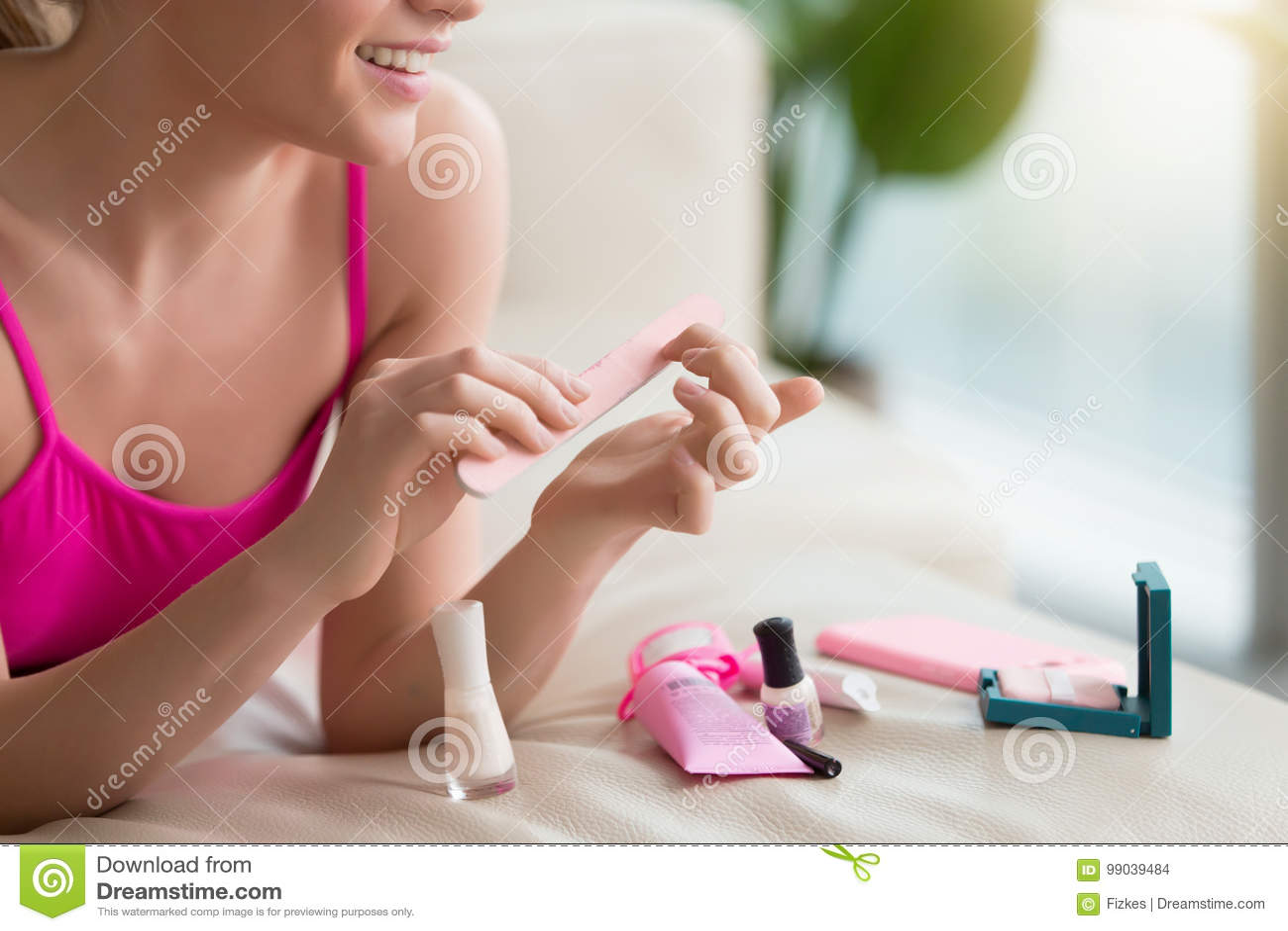Женщина используя буфер ногтя делая маникюр