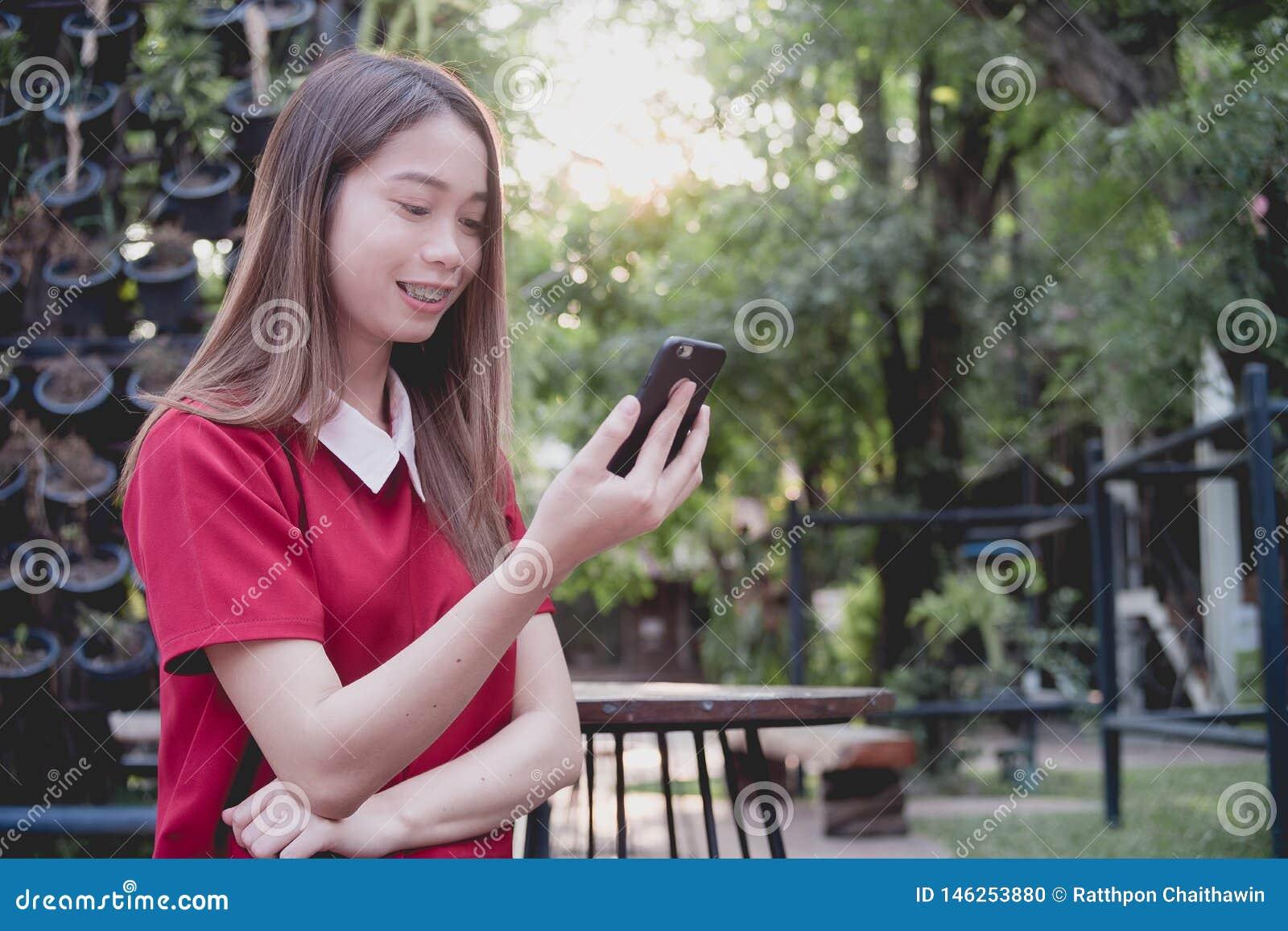 Женщина используя мобильный телефон пока стойка в парке