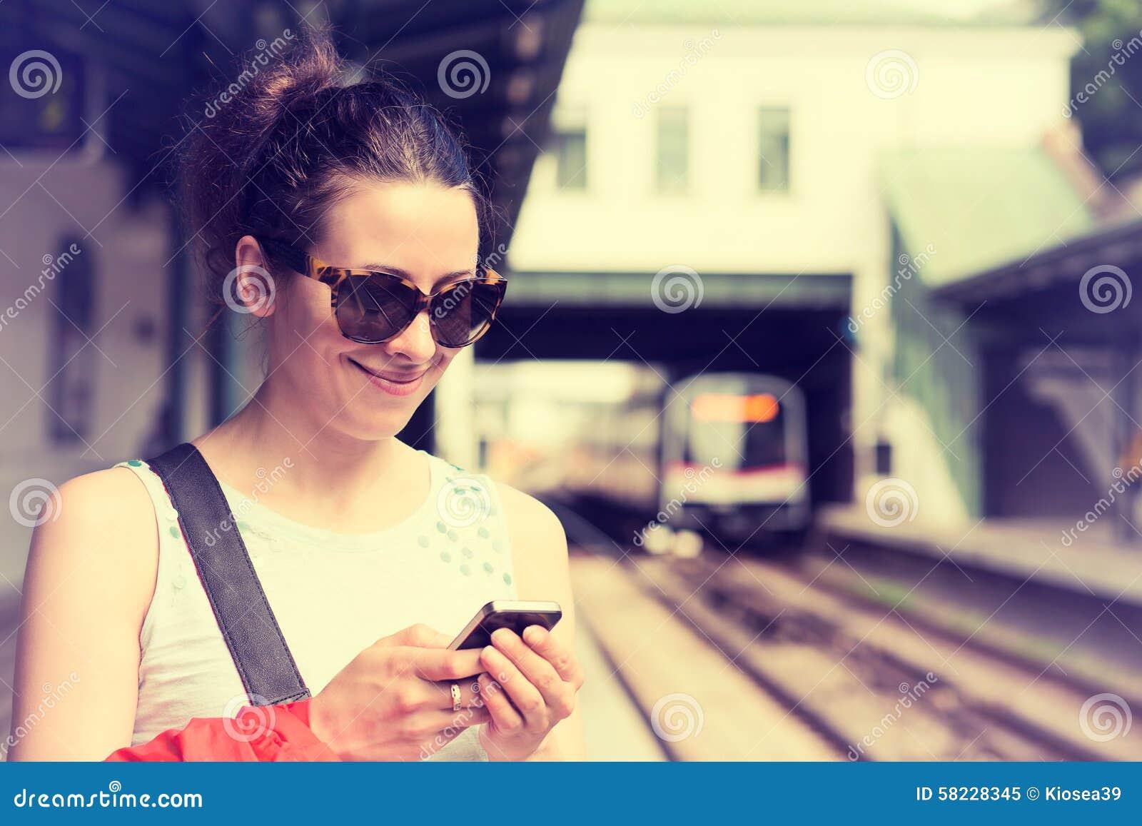 Женщина используя ее сотовый телефон на платформе метро, проверяя план-график поезда