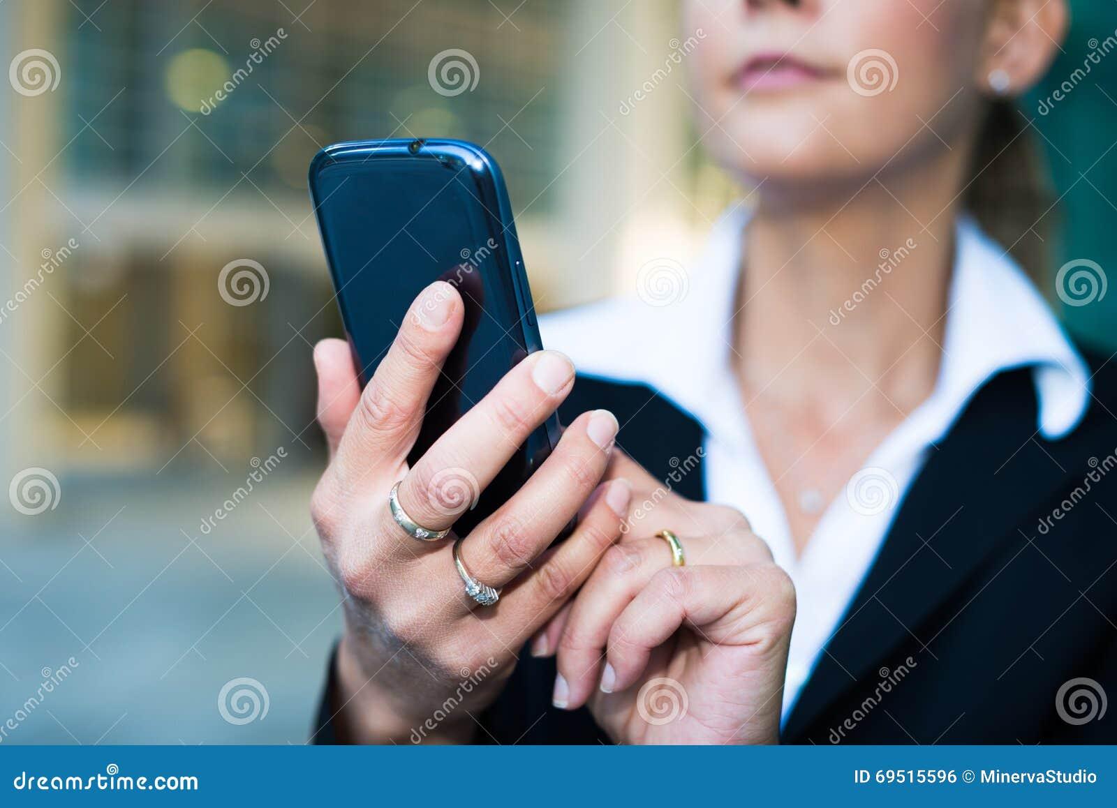 Женщина используя ее smartphone