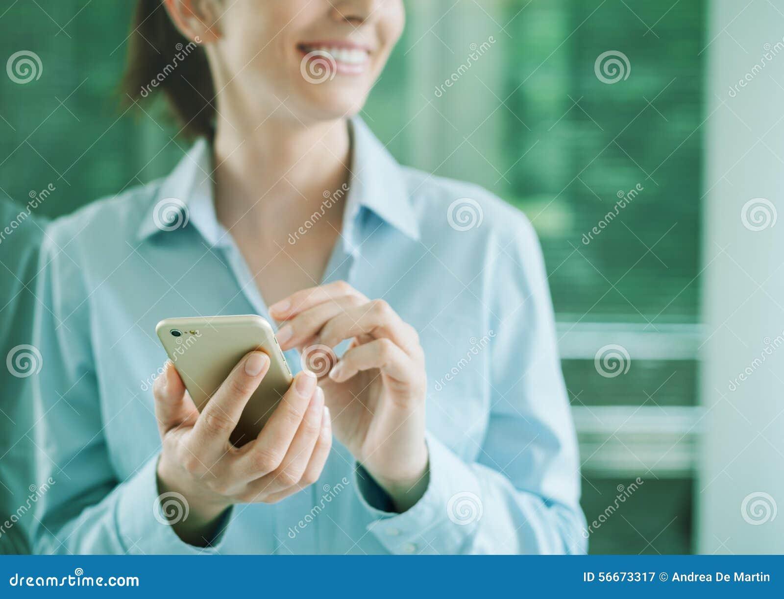 Женщина используя smartphone и полагающся на окне