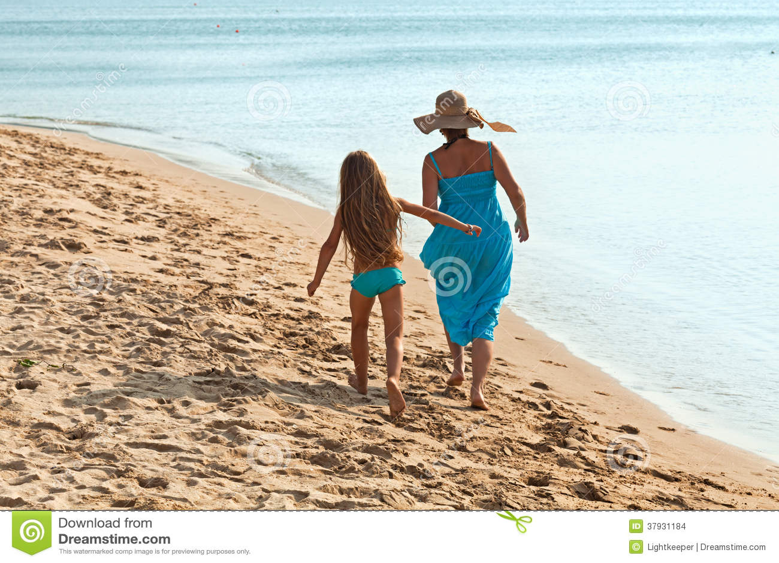 Женщина и маленькая девочка на утре идут морем